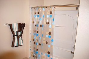Shower/tub combo with polka dot shower curtain with towel on rack