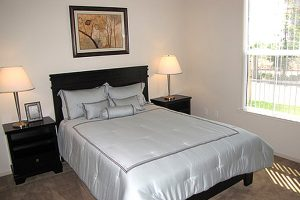 Bedroom with nightstands, lamps, and window