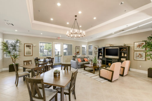 bright community room with seating areas, chandelier, television