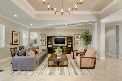 bright community room with seating areas, chandelier, television, lounge area
